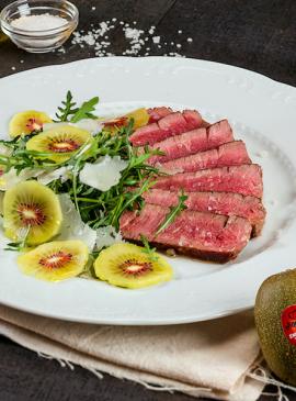 Gebratenes Rindfleisch mit Rucola, Kiwi und Parmesanblättern