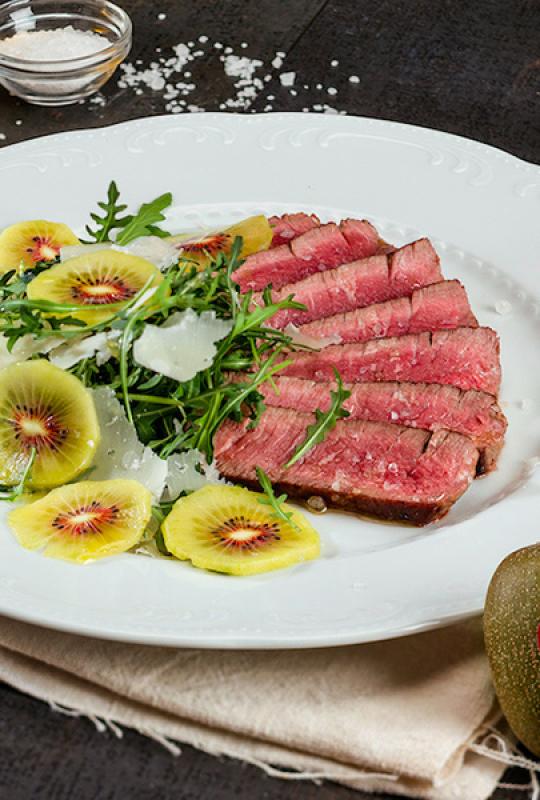 Carne bovina fatiada com rúcula, kiwi e pétalas de parmesão